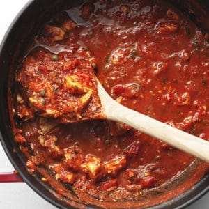 chicken cacciatore stew in a red dutch oven with a wooden spoon