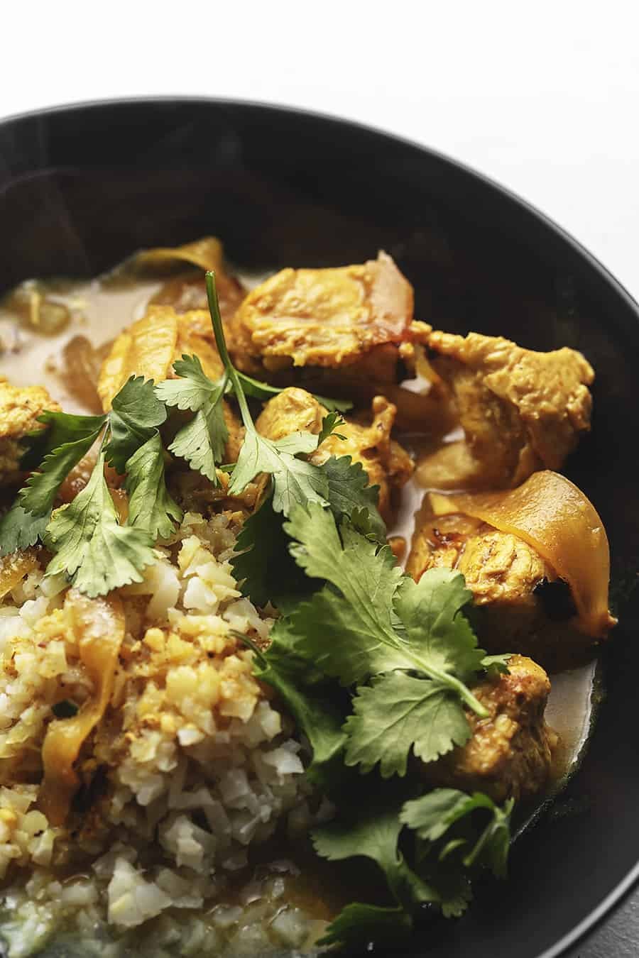 Indian curry chicken with cilantro in a black bowl