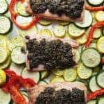 pesto topped salmon over veggies on a sheet pan