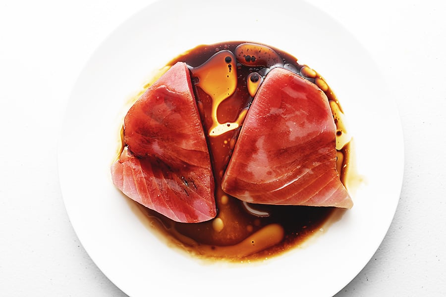 ahi tuna marinading in sesame oil and soy sauce on a white plate