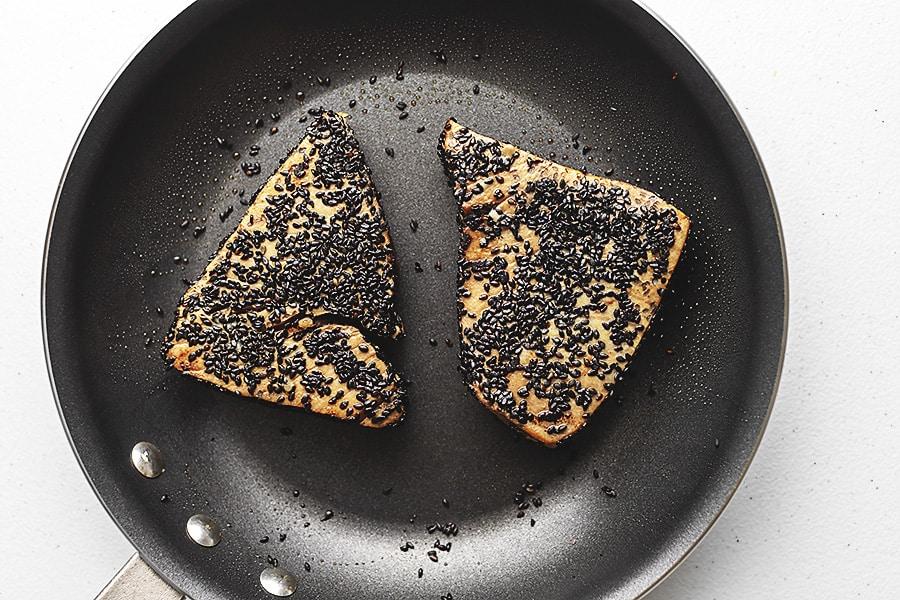 sesame crusted tuna steaks searing in a non stick skillet