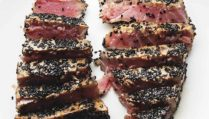 2 sesame crusted ahi tuna steaks sliced on a white plate