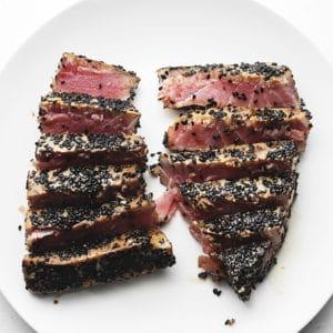 2 sesame crusted ahi tuna steaks sliced on a white plate