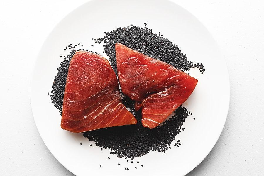 tuna steaks on a plate full of sesame seeds