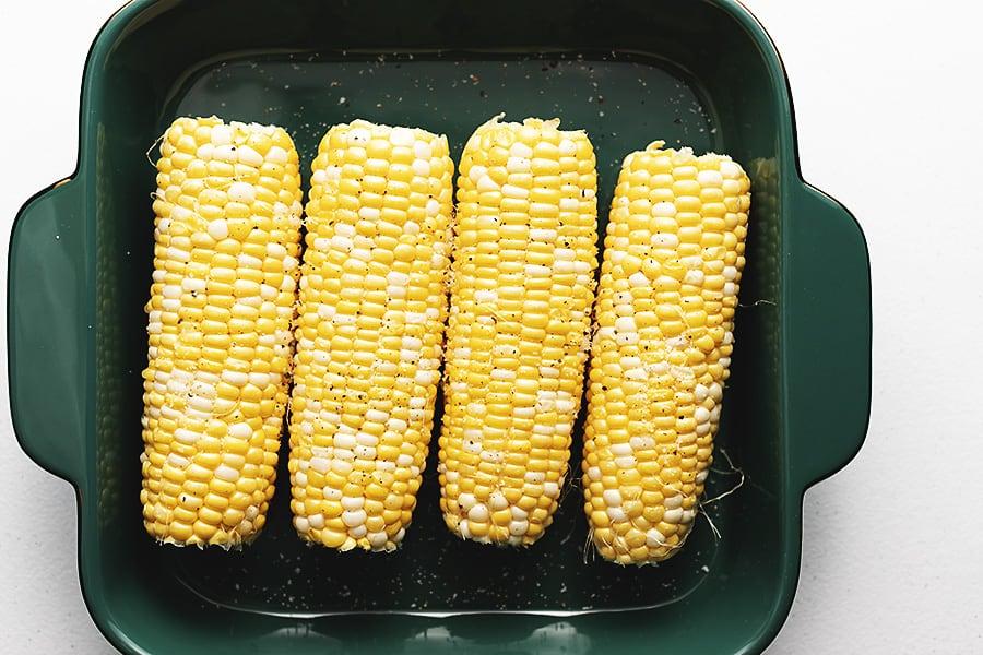 4 ears of corn in a green casserole dish