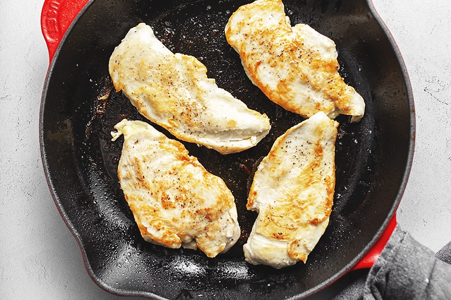 browned chicken breast in a re le creuset skillet