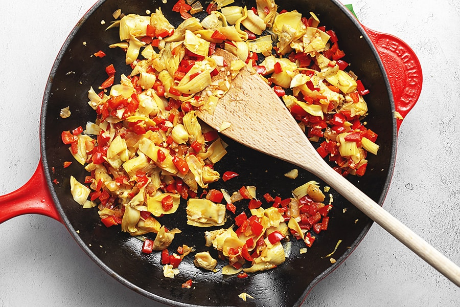 artichoke and red bell pepper sautéing in a red skillet