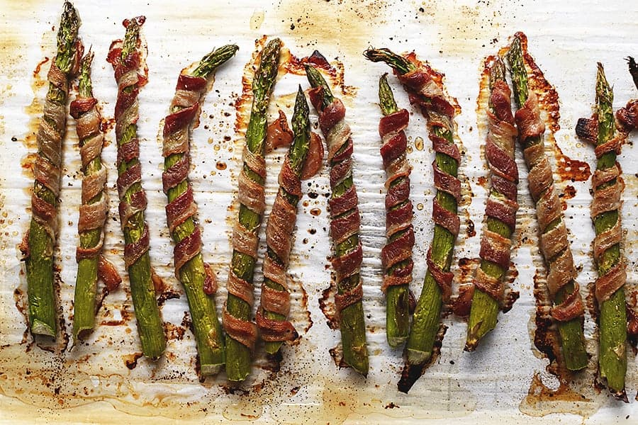 asparagus wrapped in bacon on a sheet pan