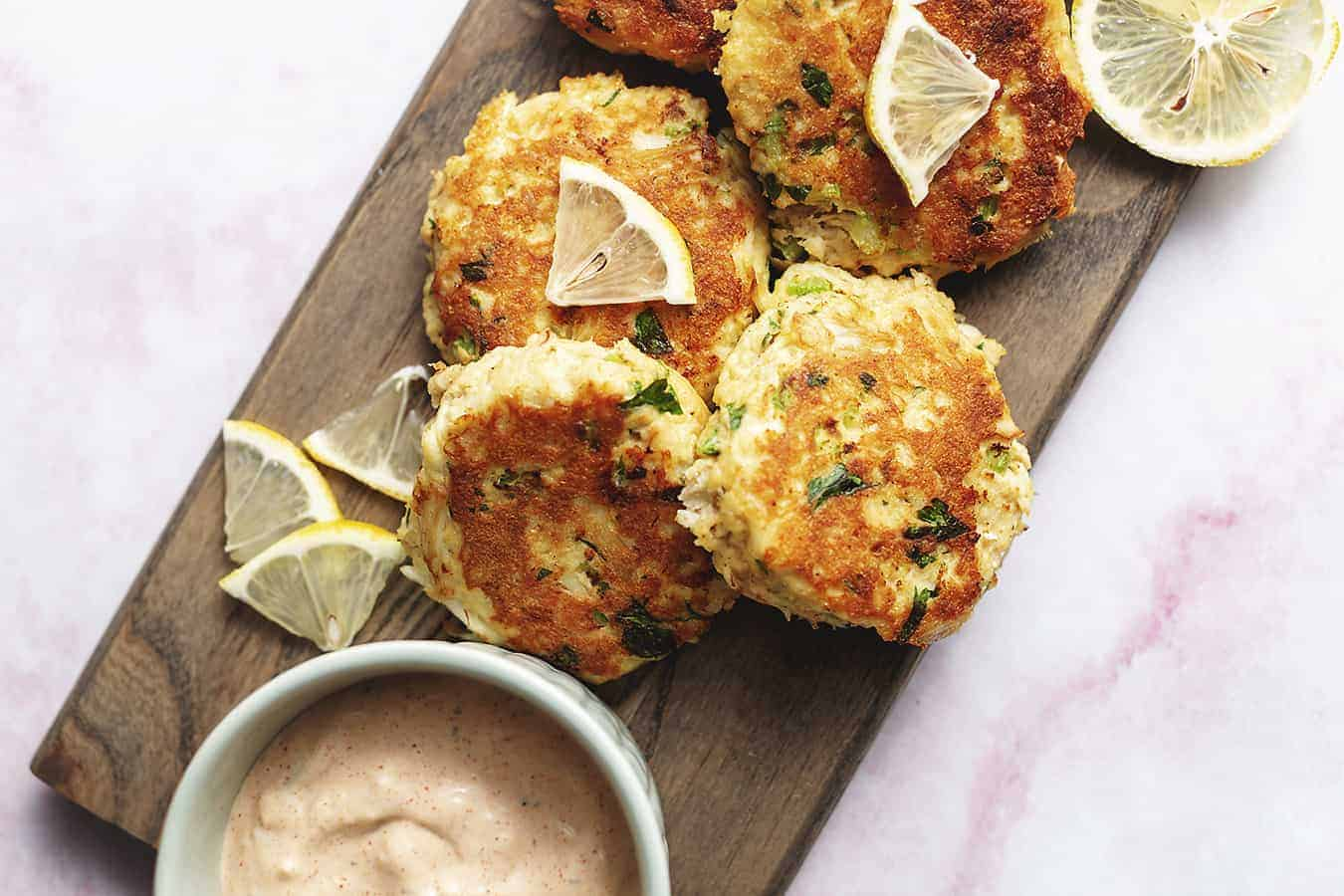 keto crab cakes garnished with remoulade sauce on a wood platter
