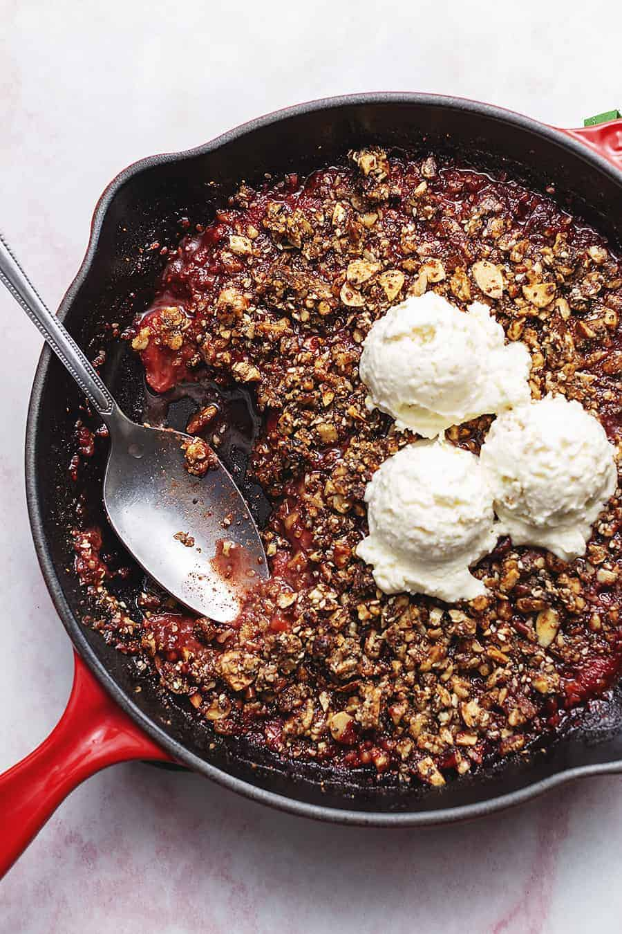 keto strawberry crisp in a skillet with ice cream