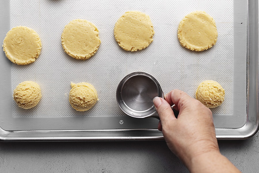 pressing sugar cookies with a measuring scoop