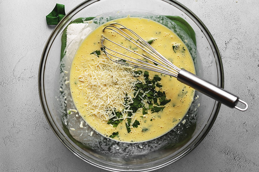 eggs, parmesan cheese, heavy cream and parsley in a glass bowl