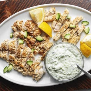 greek chicken with easy tzatziki sauce on a while platter