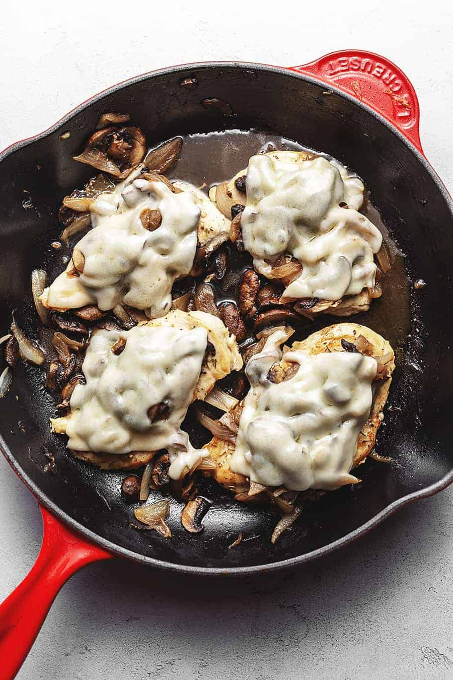 French onion smothered chicken in a cast iron skillet