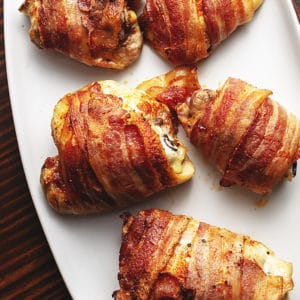 bacon wrapped chicken thighs on a white platter
