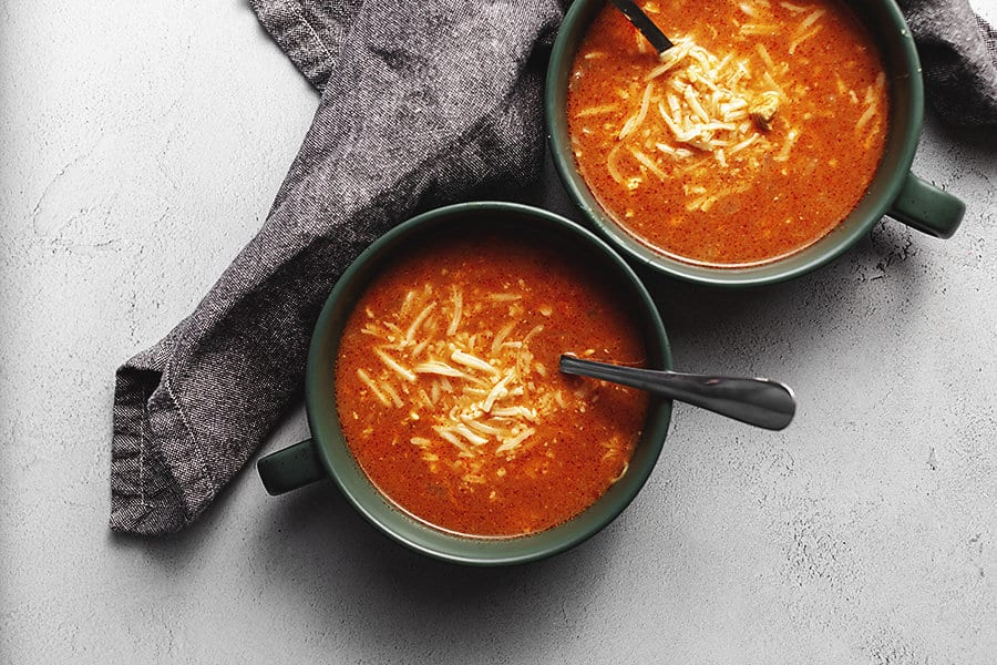 chicken enchilada soup in serving bowls with cheese