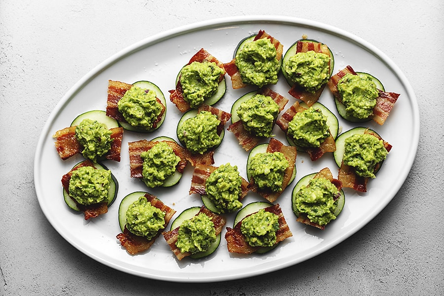 keto appetizer with cucumber, guacamole and bacon on a white platter