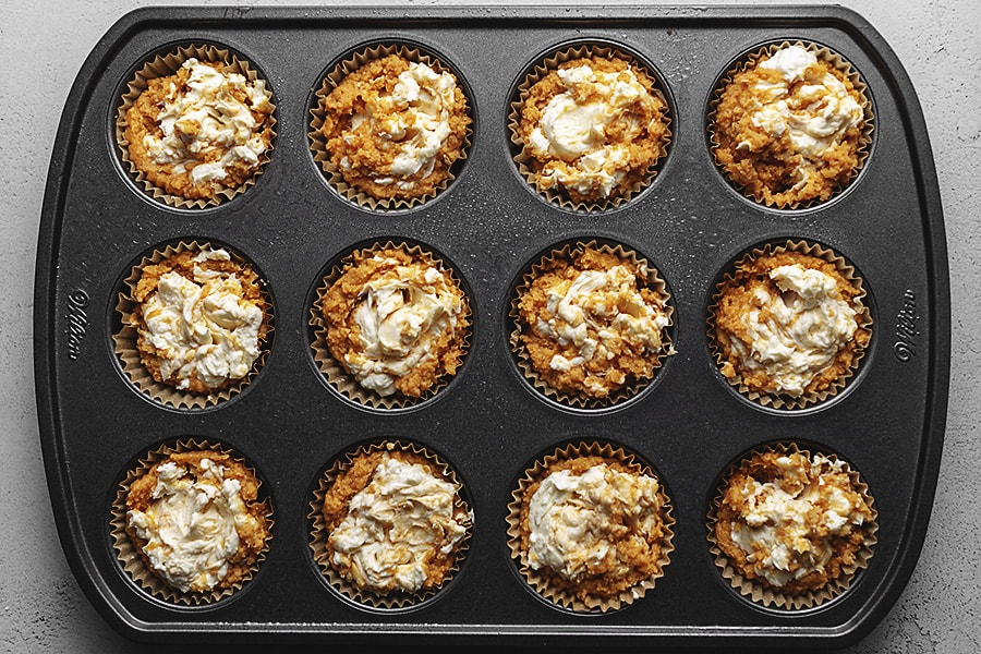 keto pumpkin cheesecake muffins in a muffin pan ready to be baked