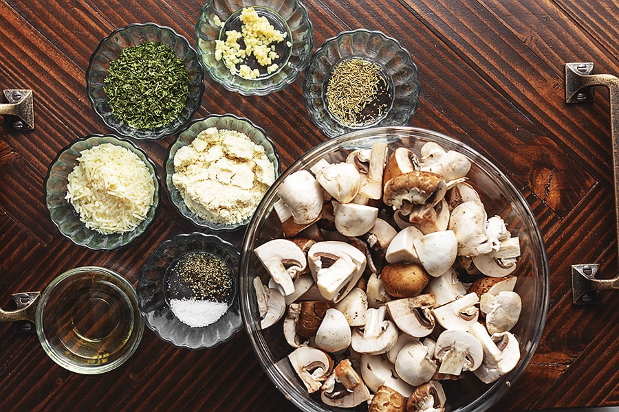 roasted mushrooms ingredients in glass bowls on a wood platter