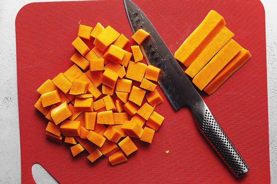 butternut squash being cut on a red cutting board