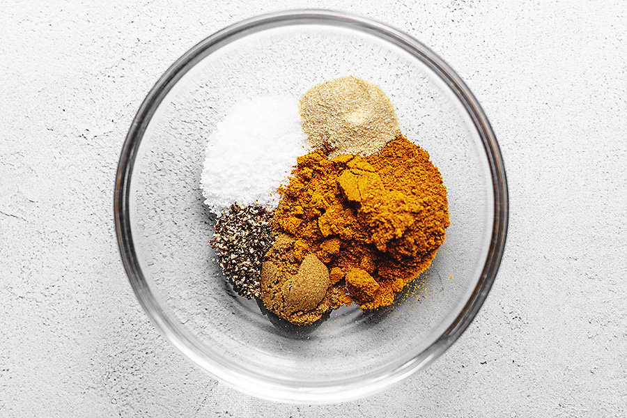 spices in a glass bowl for curry roasted chicken thighs with butternut squash and cauliflower