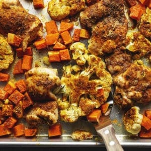 curry roasted chicken thigh with butternut squash and cauliflower on a sheet pan