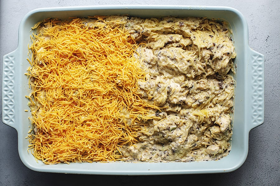baked chicken spaghetti with squash in a casserole dish spreading cheese on top