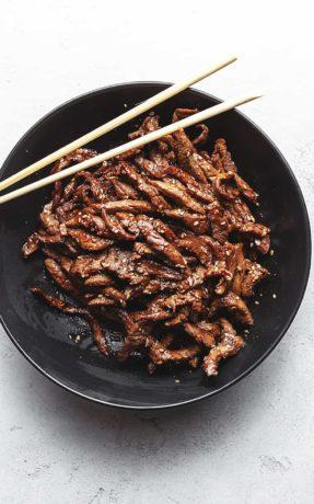 keto beef bulgogi in a black bowl with chopsticks