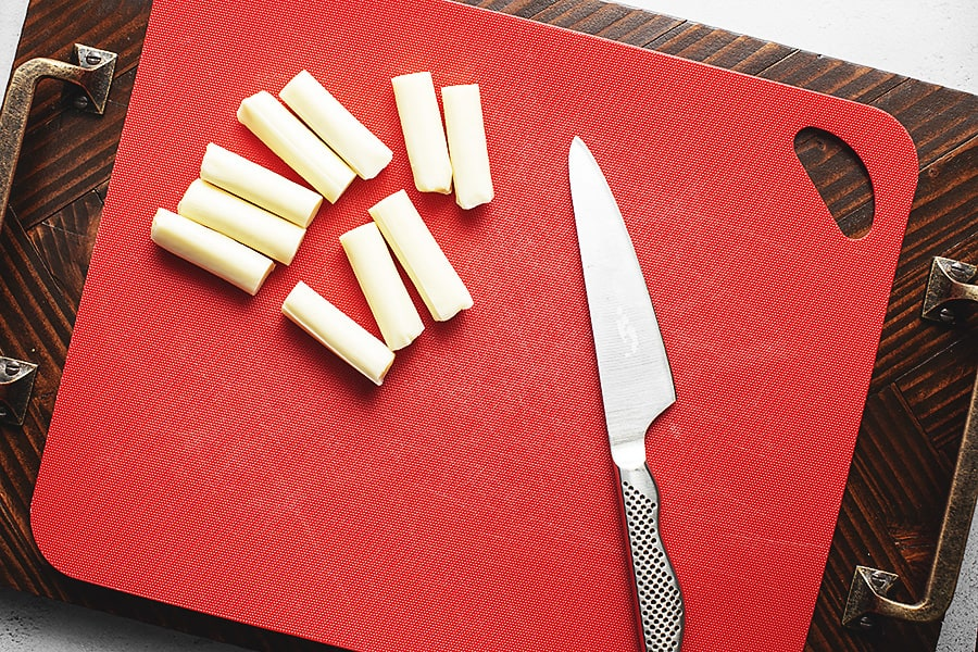 mozzarella cheese sticks cut in half on a red cutting board