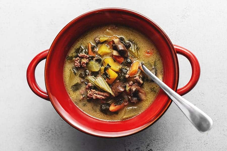 autumn vegetable beef soup in a red soup bowl