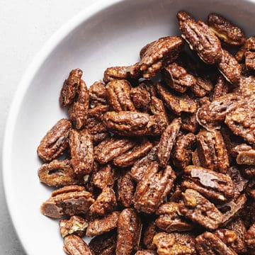 keto candied pecans in a white glass bowl