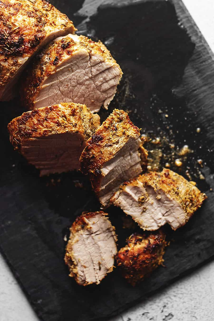 air fryer pork tenderloin cut on a black board