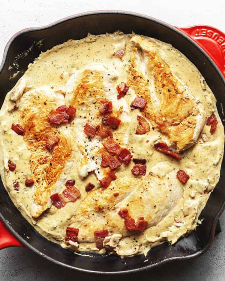 cream cheese chicken with bacon in a red skillet