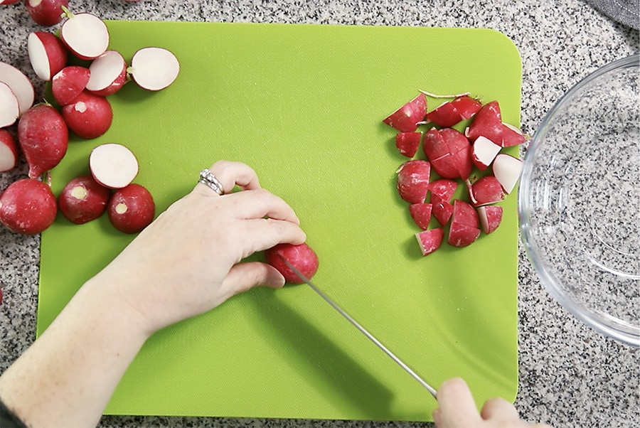 cutting radishes into quarter size chunks on a green cutting board