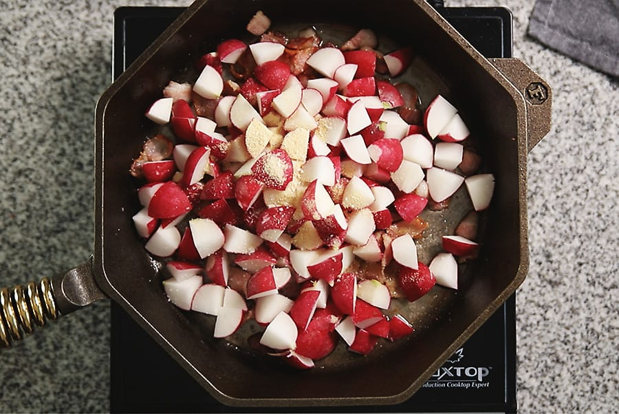 radishes with bacon being fried in a skillet