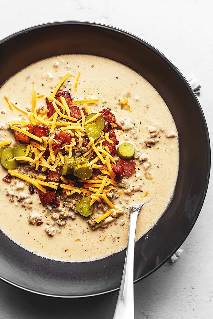 A CREAMY SOUP WITH HAMBURGER, BACON, CHEESE, AND PICKLES IN A BLACK BOWL