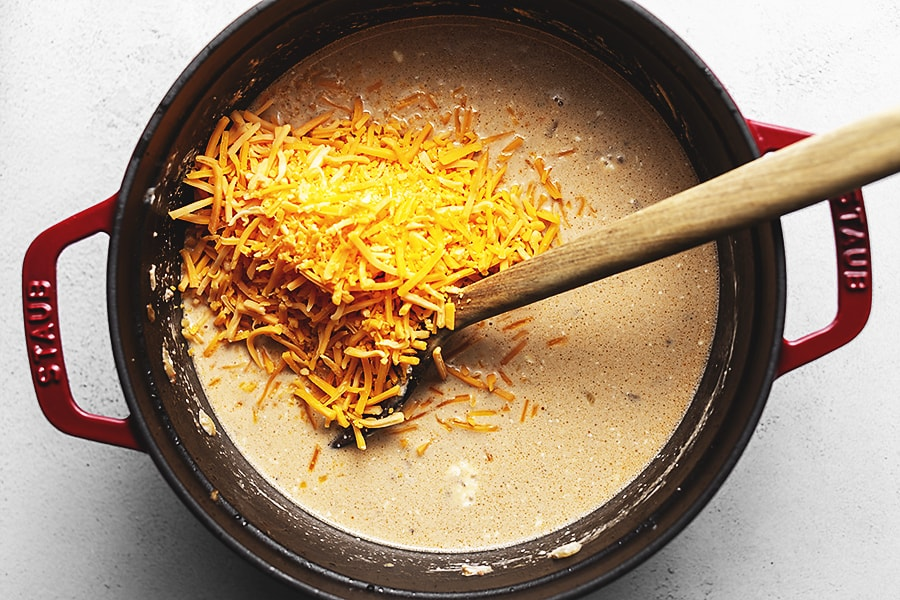 cheese being added to a creamy soup in a red dutch oven