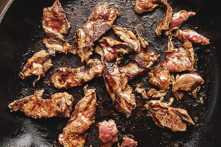 flatiron steak cooking in a skillet