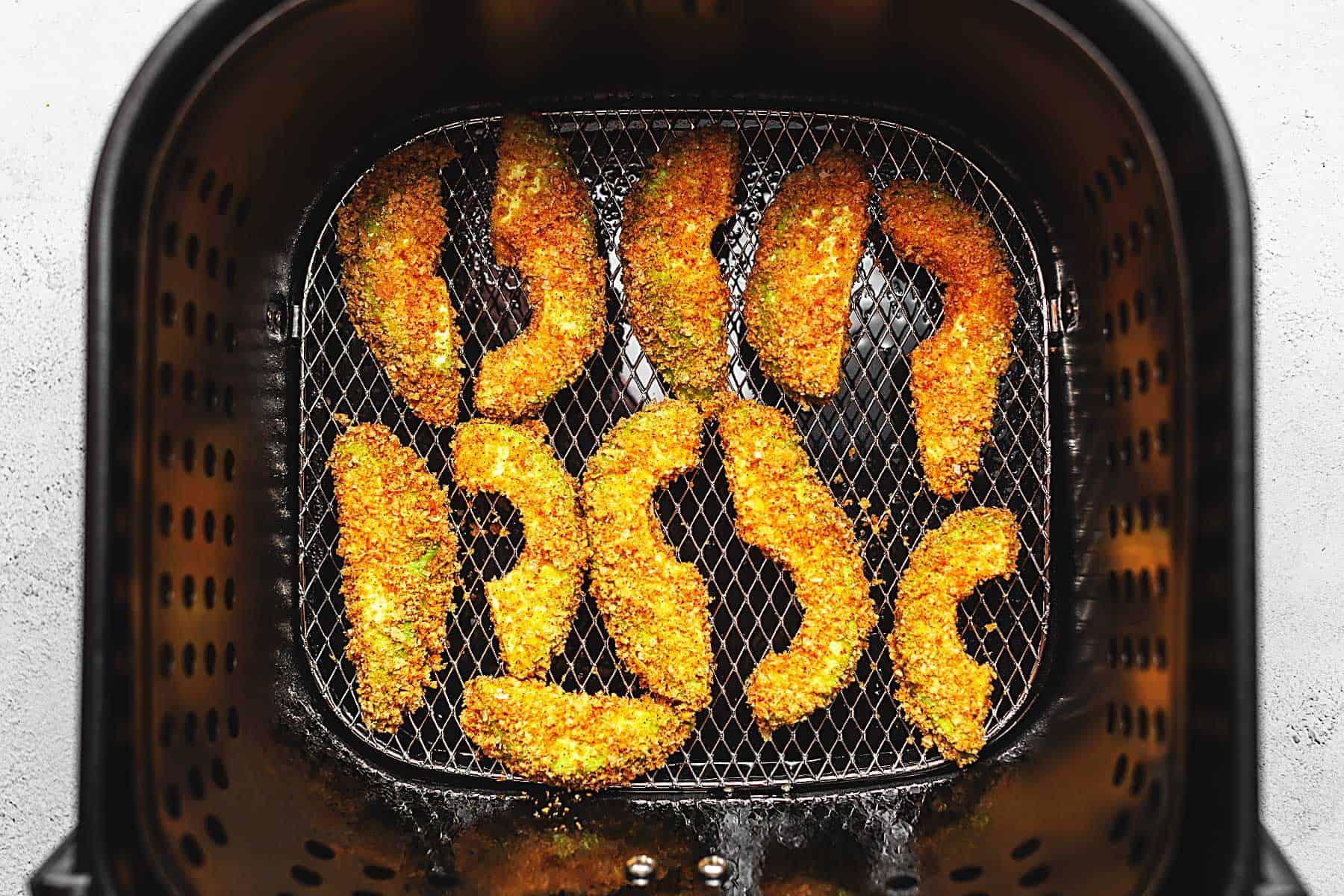 avocado fries in the air fryer basket.
