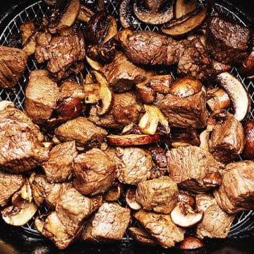 steak and mushrooms in an air fryer basket