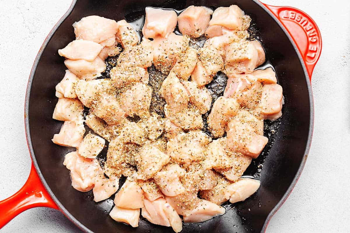 raw chicken in a red skillet for low carb chicken alfredo