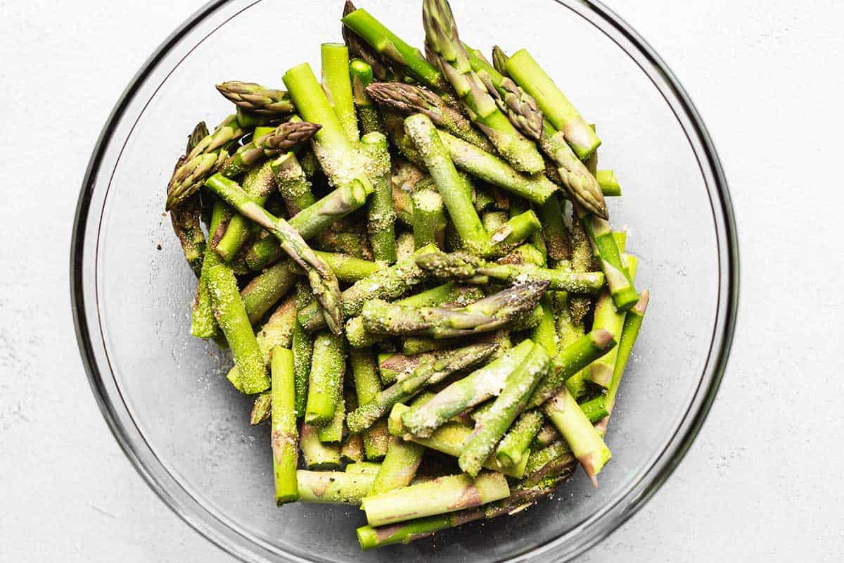 mixing asparagus with seasoning in a glass bowl
