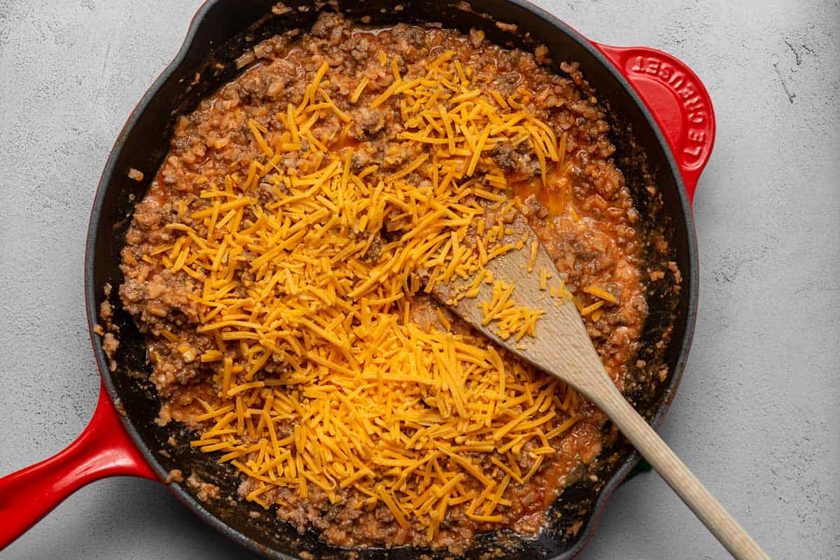 cheese on top of seasoned ground beef in a red skillet