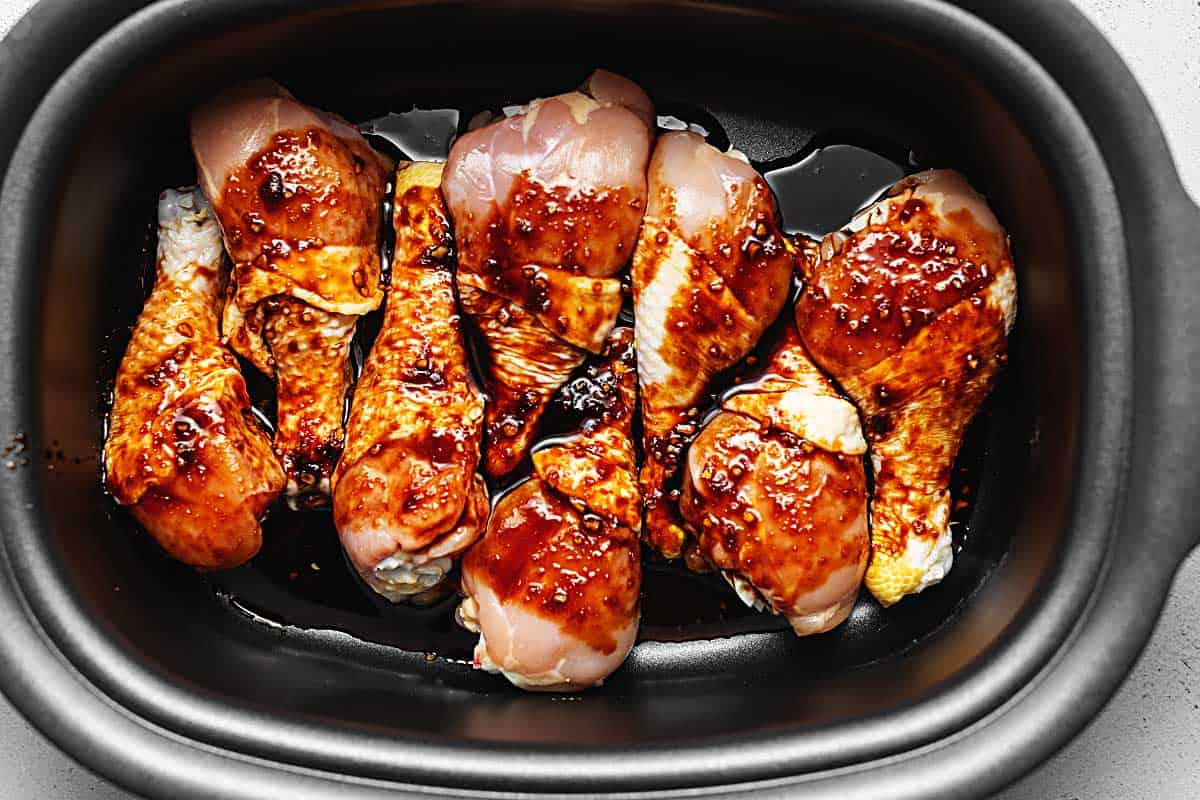 chicken drumsticks in a slow cooker covered in a sauce