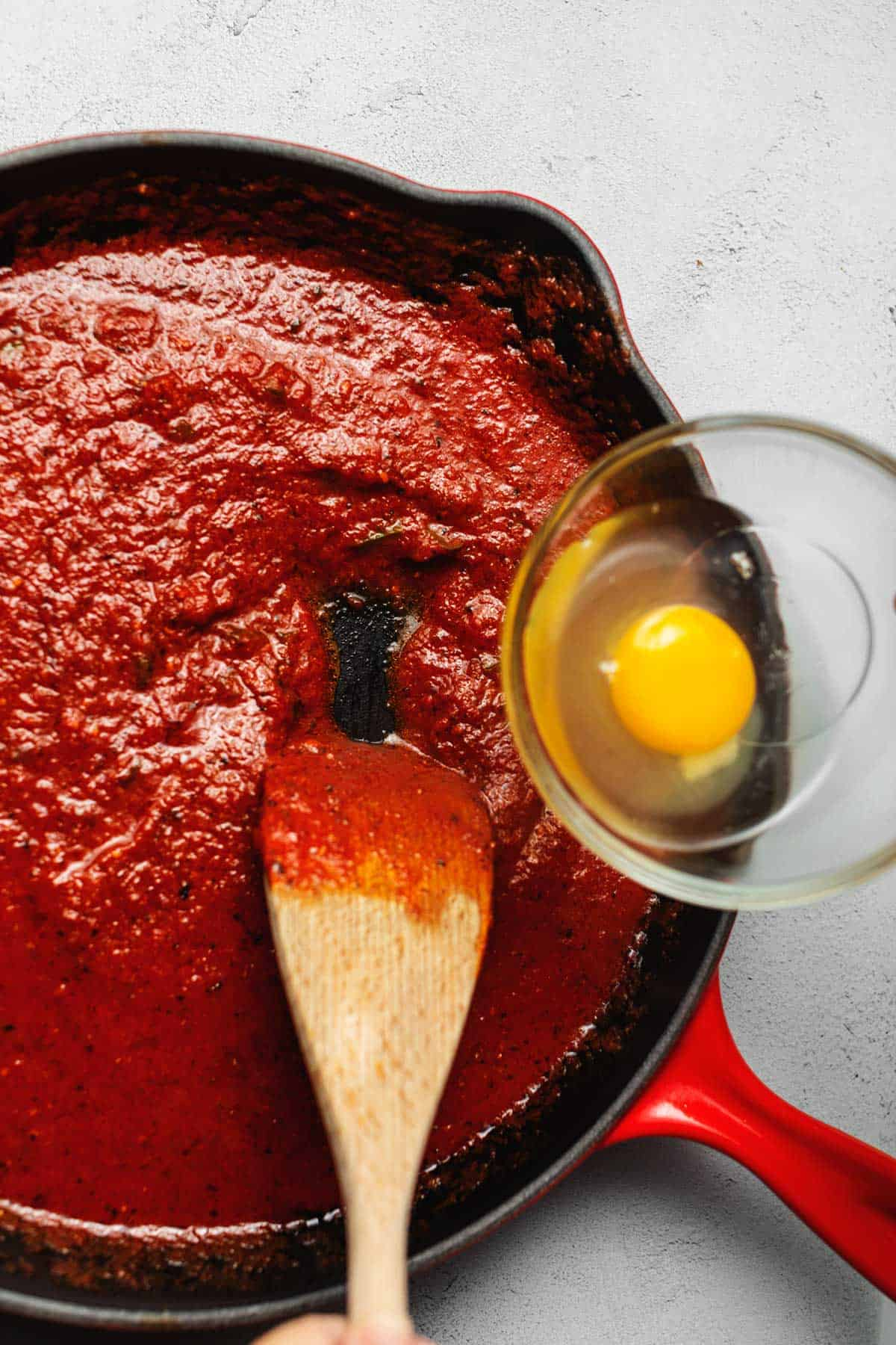 eggs being placed in marinara sauce for shakshuka