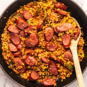 sausage and peppers in a red skillet
