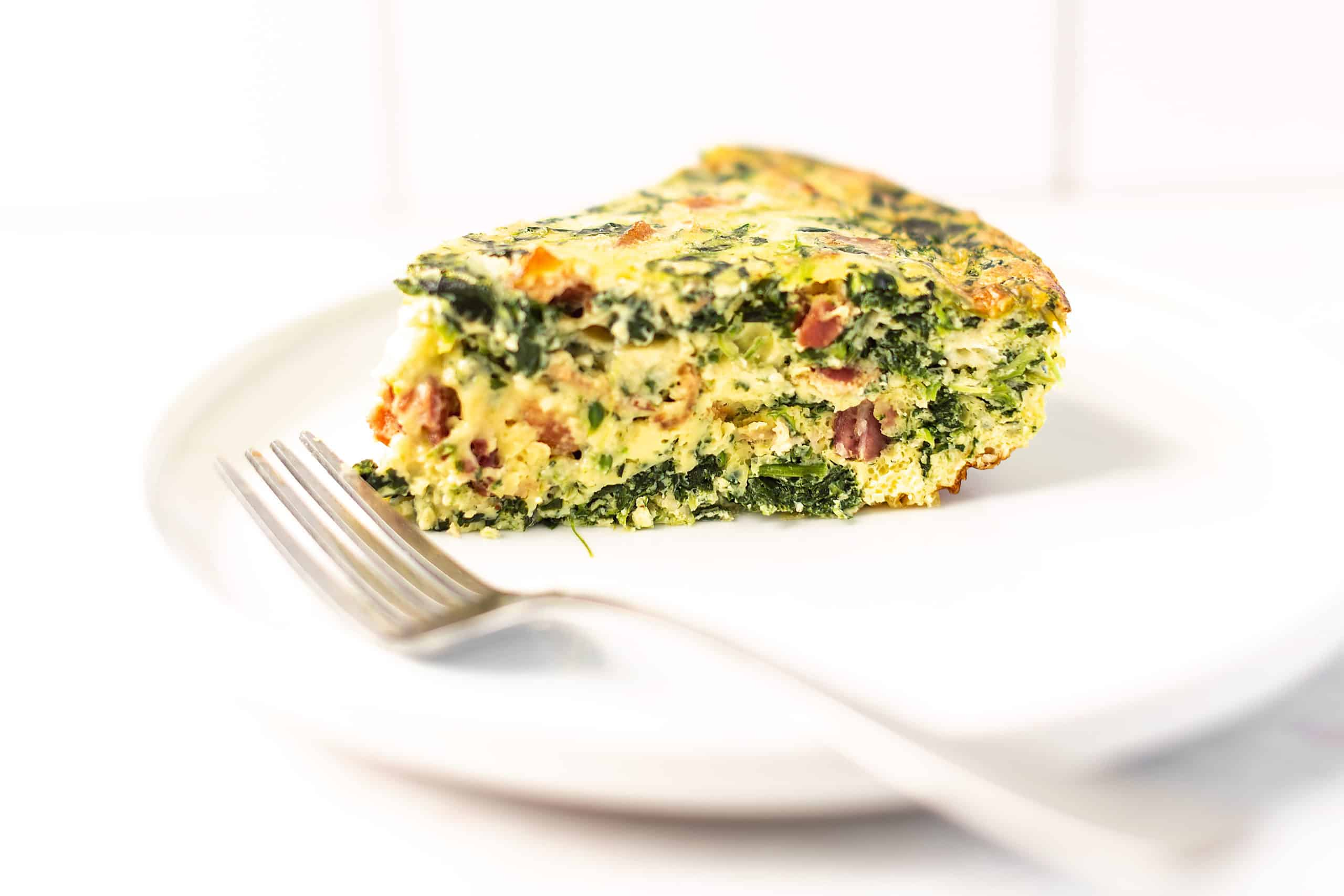 spinach and bacon quiche on a white plate