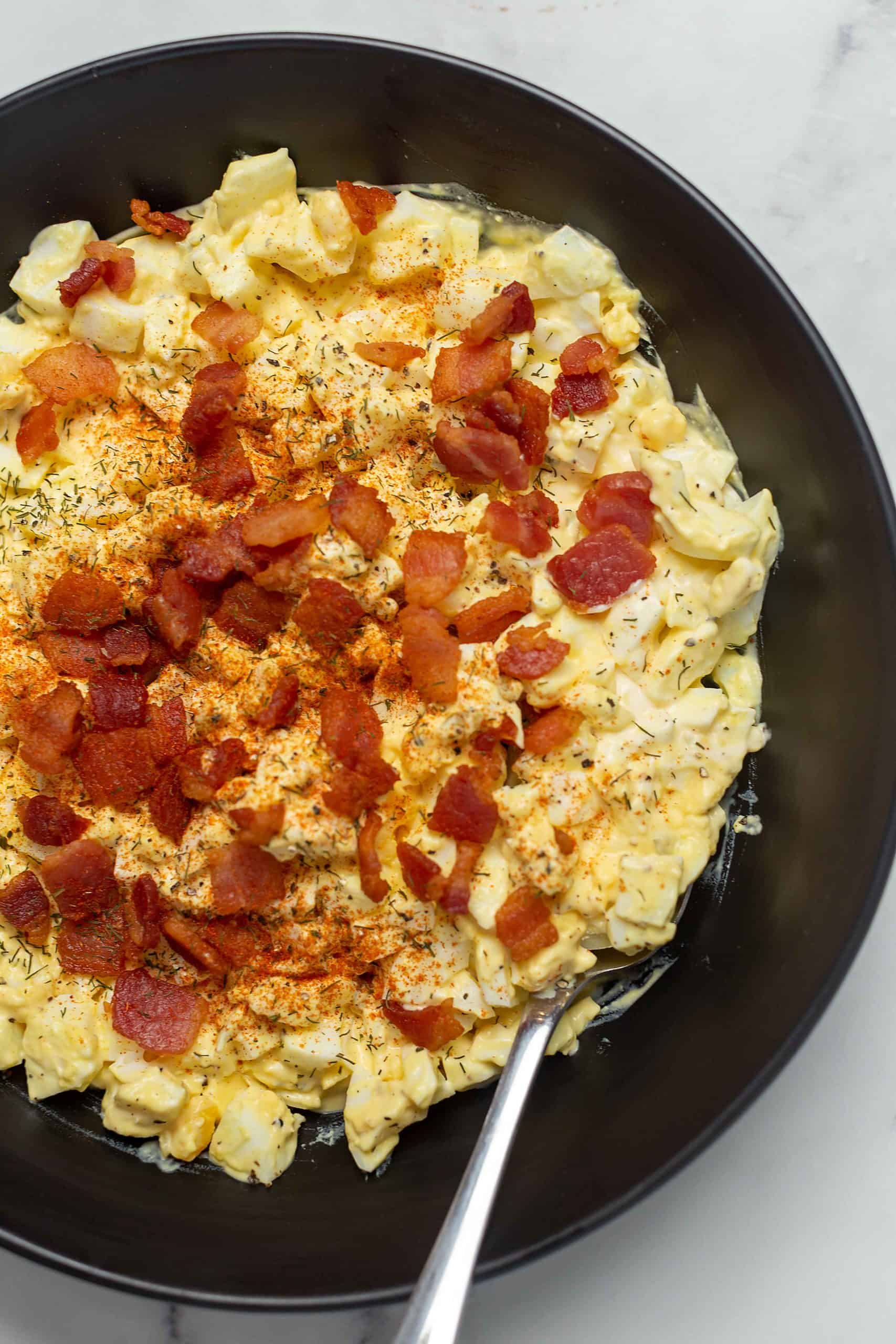 keto egg salad with bacon in a black bowl