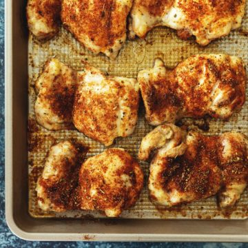 baked boneless chicken thighs on a blue background